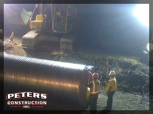 Installing a new roadway cross culvert at night in Old Orchard Beach